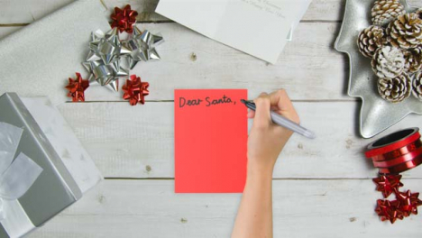 Top-Down-View-of-Hand-Writing-Dear-Santa-On-Paper-with-Christmas-Gifts-and-Cards