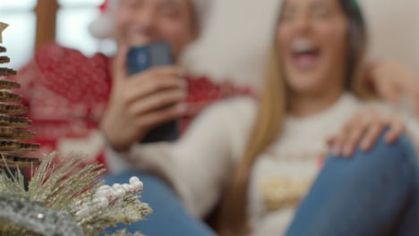 Extreme-Close-Up-of-Christmas-Decorations-As-Couple-In-Background-Use-Teléfono