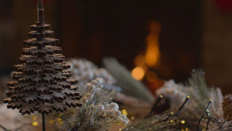 Extreme-Close-Up-Shot-of-Table-Christmas-Decorations-In-Front-of-Cosy-Fire