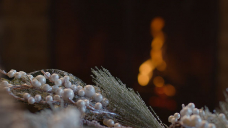 Extreme-Close-Up-Shot-of-Table-Christmas-Decorations-In-Front-of-Cosy-Fireplace
