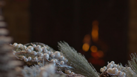 Extreme-Close-Up-Shot-of-Table-Christmas-Ornaments-In-Front-of-Cosy-Fireplace
