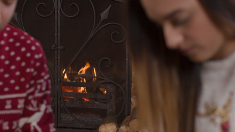 Sliding-Shot-of-Burning-Fireplace-Behind-Young-Couple-Wrapping-Christmas-Presents