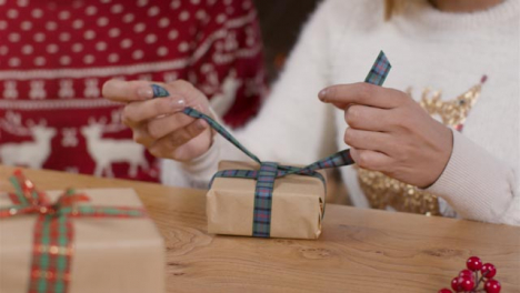 Close-Up-Shot-of-Young-Womans-Hands-Wrapping-Ribbon-On-Christmas-Present