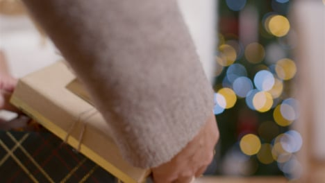 Extreme-Close-Up-of-Young-Womans-Hands-Opening-Christmas-Present