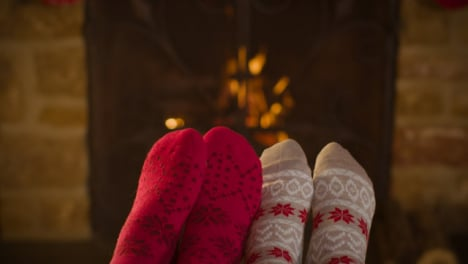 Close-Up-Shot-of-Couples-Feet-In-Front-of-Burning-Fireplace