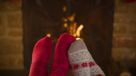 Close-Up-Shot-of-Couples-Feet-In-Front-of-a-Burning-Fireplace