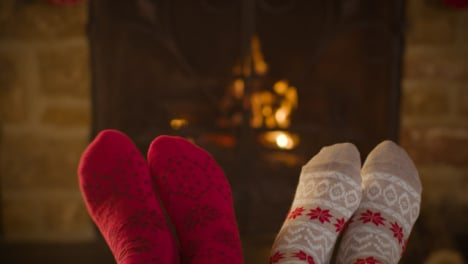 Close-Up-Shot-of-Couples-Feet-In-Front-of-a-Cosy-Burning-Fireplace