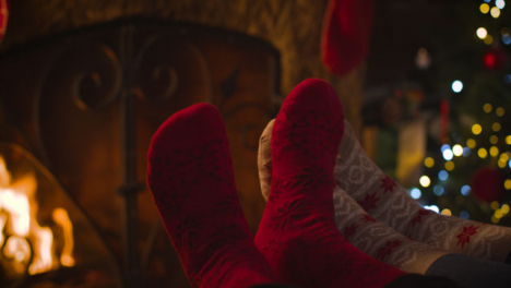 Close-Up-Shot-of-Couples-Feet-In-Front-of-Cosy-Burning-Fireplace