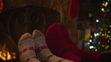 Close-Up-Shot-of-Couples-Feet-In-Front-of-Cosy-Burning-Fire