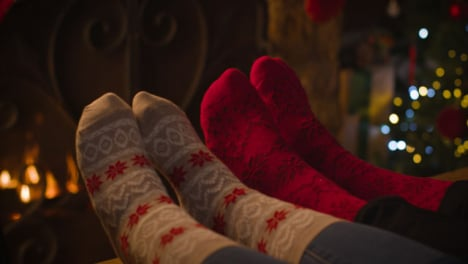 Close-Up-Shot-of-Couples-Feet-In-Front-of-a-Cosy-Burning-Fire