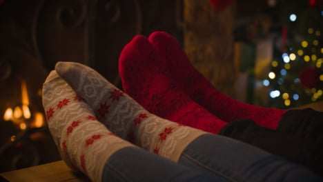 Close-Up-Shot-of-Couples-Feet-In-Front-of-Cosy-Warm-Fireplace