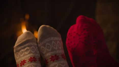 Extreme-Close-Up-Shot-of-Couples-Feet-In-Front-of-Burning-Fireplace