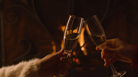 Close-Up-of-Two-People-Bringing-Their-Champagne-Glasses-Together-In-Front-of-Fire