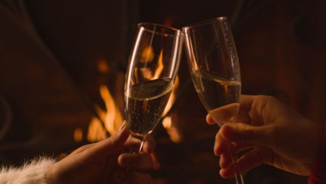 Close-Up-of-Two-People-Bringing-Their-Champagne-Glasses-Together-In-Front-of-Burning-Fire-