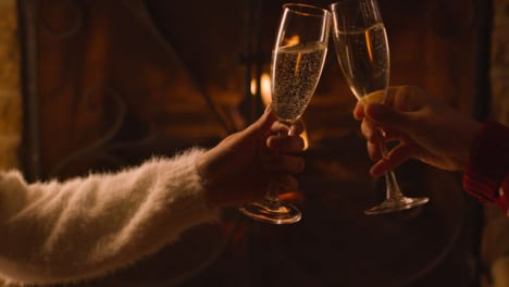 Close-Up-of-Two-People-Bringing-Their-Champagne-Glasses-Together-In-Front-of-Burning-Fireplace