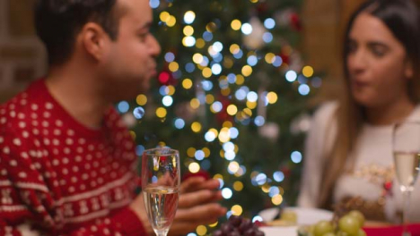 Defocused-Shot-of-Young-Couple-Enjoying-Food-Spread-During-Christmas-Celebrations-