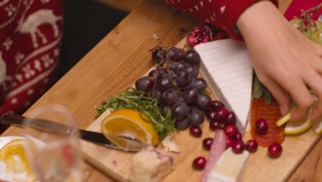 Panning-Shot-Over-Table-Top-Food-Spread-As-Two-People-Pick-From-It