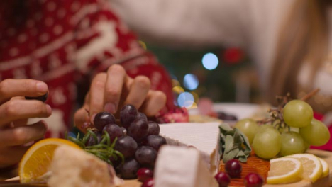 Extreme-Close-Up-Shot-of-Christmas-Table-Top-Food-Spread-with-Couple-In-Background