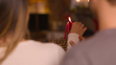 Over-the-Shoulder-Shot-of-Young-Couple-Lighting-Candles-of-Menorah-During-Hanukkah