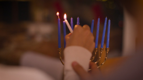 Over-the-Shoulder-Shot-of-Couple-Lighting-Candles-of-Menorah-During-Hanukkah