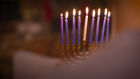Over-the-Shoulder-Shot-of-Young-Couple-Looking-at-Lit-Menorah-During-Hanukkah