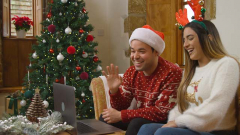 Wide-Shot-of-Young-Couple-Talking-to-Laptop-Camera-During-Christmas-Video-Call-