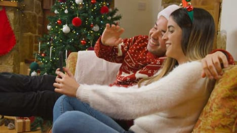 Medium-Shot-of-Young-Couple-Waving-and-Talking-to-Phone-Camera-During-a-Christmas-Video-Call