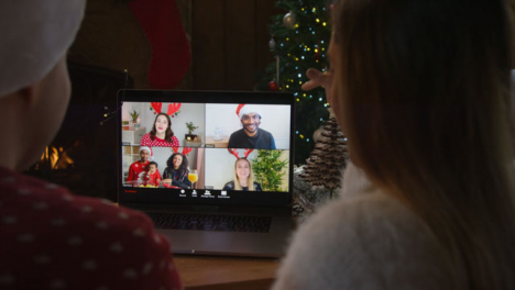 Over-the-Shoulder-Shot-of-Couple-Talking-to-Friends-On-Laptop-Christmas-Video-Call