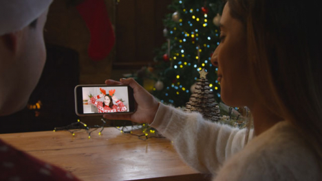 Over-the-Shoulder-Shot-of-Couple-Talking-to-Friend-On-Mobile-Phone-Christmas-Video-Call
