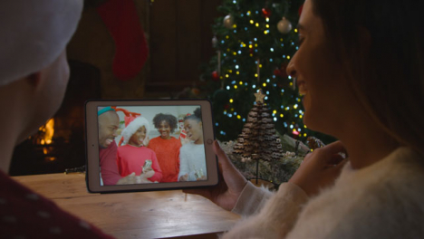 Over-the-Shoulder-Shot-of-Couple-Waving-and-Talking-to-Family-Friends-On-Christmas-Video-Call