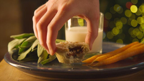 Sliding-Extreme-Close-Up-Shot-of-Hand-Taking-Away-Mince-Pie-and-Milk-From-Plate-