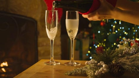 Sliding-Close-Up-Shot-of-Female-Hands-Pouring-Two-Glasses-of-Champagne-From-Bottle