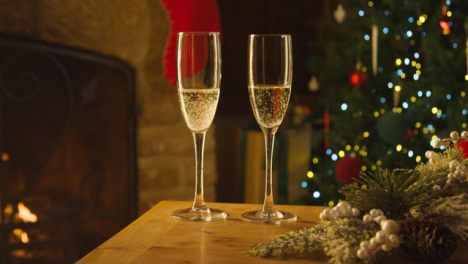Close-Up-of-Two-Glasses-of-Champagne-On-Table-In-Front-of-Fireplace