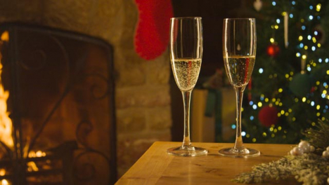 Sliding-Close-Up-of-Two-Glasses-of-Champagne-On-Table-In-Front-of-Fireplace