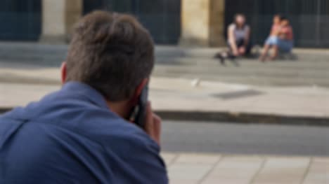 Defocused-Shot-of-Man-Talking-On-Phone-Whilst-Sitting-On-Street-In-Oxford-01