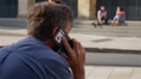 Defocused-Shot-of-Man-Talking-On-Phone-Whilst-Sitting-On-Street-In-Oxford-02