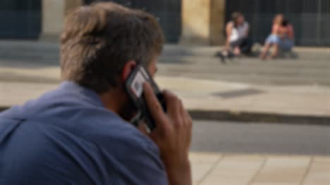 Defocused-Shot-of-Man-Talking-On-His-Phone-Whilst-Sitting-On-Street-In-Oxford-01
