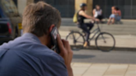 Defocused-Shot-of-Man-Talking-On-His-Phone-Whilst-Sitting-On-Street-In-Oxford-02