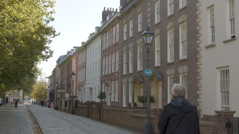 Sliding-Shot-of-Man-Walking-Down-Picturesque-Street-In-Bristol-England