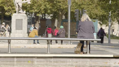 Wide-Shot-of-People-Sitting-On-Benches-On-Broad-Quay-In-Bristol-England