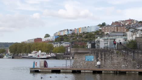 Wide-Shot-of-Young-Man-Walking-Up-Steps-at-Bristol-Harbour-In-Bristol-England