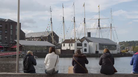 Tracking-Shot-Approaching-People-Sitting-On-Waterfront-at-Bristol-Harbour-