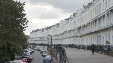 Sliding-Shot-of-Man-Walking-Past-Royal-York-Crescent-Town-Houses-In-Bristol-England