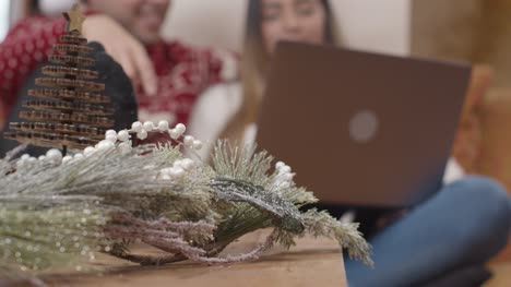 Extreme-Close-Up-of-Christmas-Decorations-As-Couple-In-Background-Interact-with-Laptop