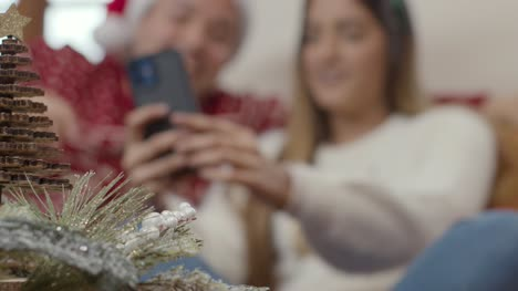 Extreme-Close-Up-of-Christmas-Decorations-As-Couple-In-Background-Interact-with-Phone