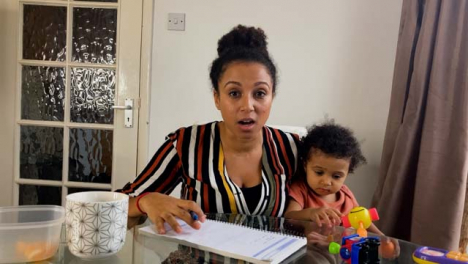 Young-Woman-with-Small-Child-On-Business-Video-Call-Briefing-Others-Whilst-Looking-Directly-to-Camera