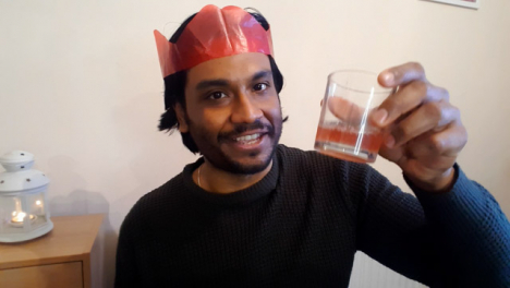 Young-Man-On-Christmas-Video-Call-Talking-and-Raising-Glass-to-Camera-
