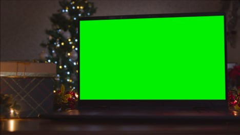 Close-Up-Shot-of-Laptop-Green-Screen-On-Table-In-Front-of-Christmas-Themed-Backdrop