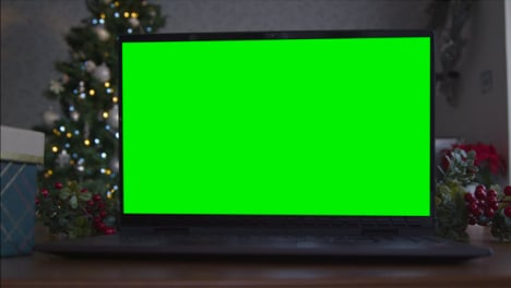 Close-Up-Shot-of-a-Laptop-Green-Screen-On-Table-In-Front-of-Christmas-Themed-Background