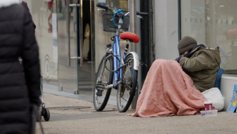 Long-Shot-of-Homeless-Person-Sitting-On-Ground-On-Busy-Street-In-Oxford-England